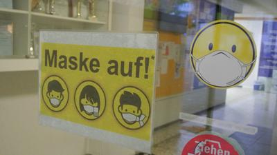 Hinweisschilder für Masken an einer Glastür