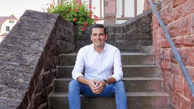 Ein junger Mann sitzt lächelnd auf einer Kirchentreppe