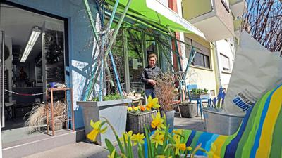 Mit einer Kette hat Silke Wilhelm den Eingang zu ihrem Laden versperrt. Dafür stehen draußen Blumen und Gestecke, bezahlt wird per Einwurf in den Briefkasten.