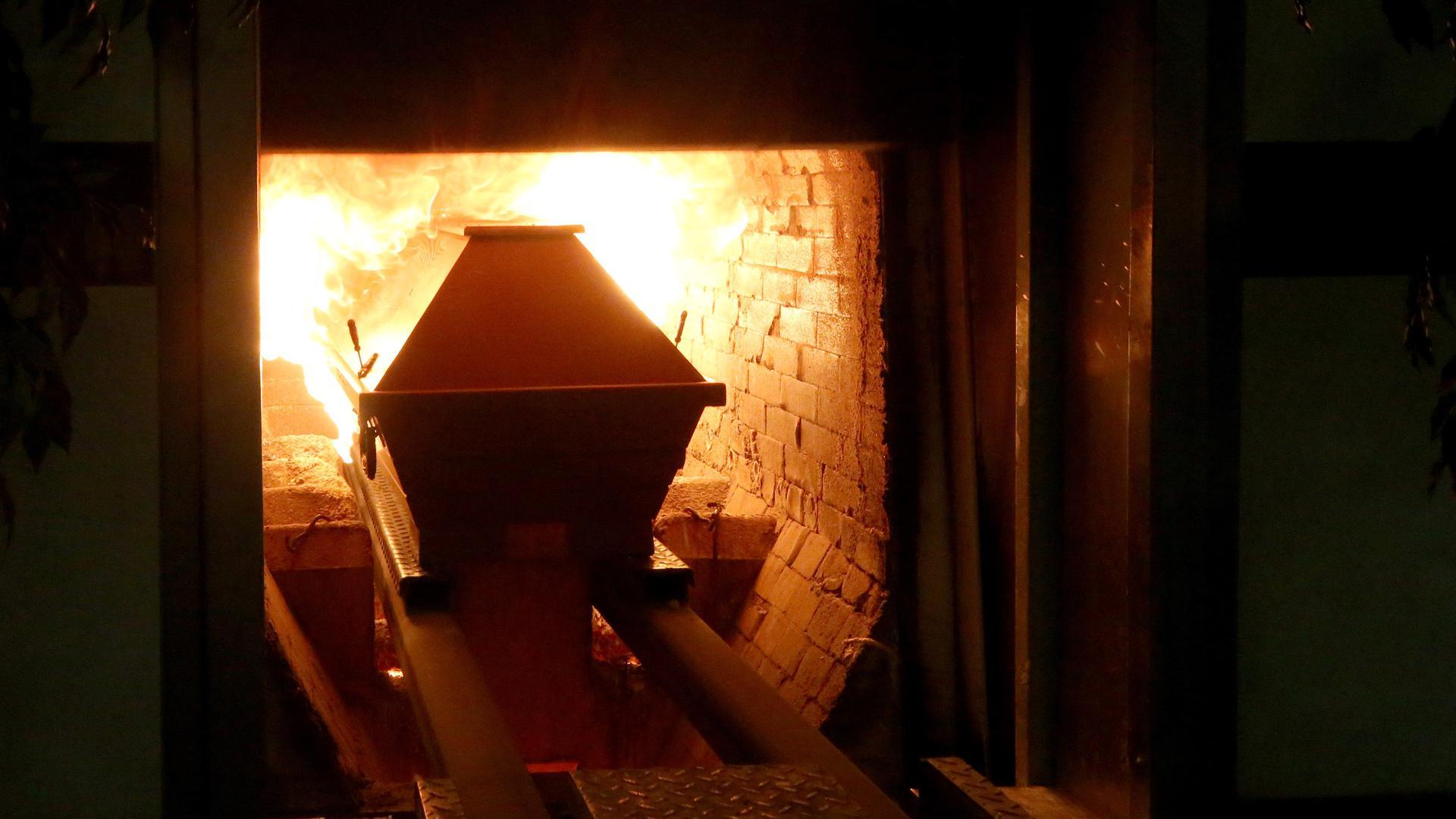 Ein Sarg wird in den rund 850 Grad heißen Krematoriumsofen gefahren.
