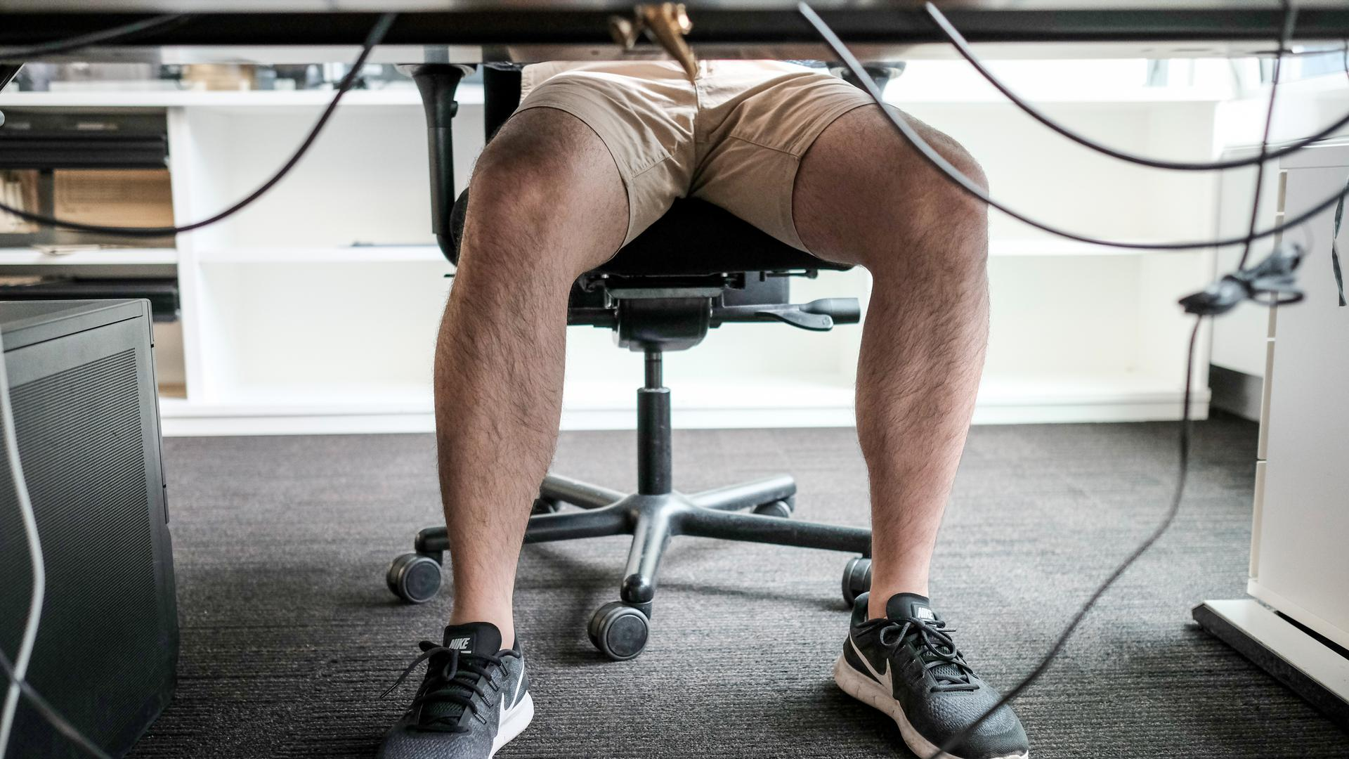 Ein Mann sitzt mit kurzer Hose an seinem Arbeitsplatz.