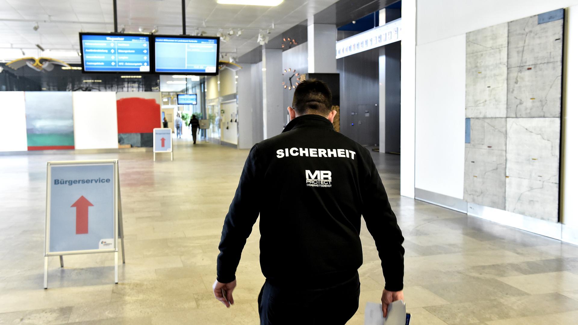 Nach Priorität und Absprache: Im Landratsamt Karlsruhe gehört der rege Besucherverkehr in der Corona-Krise vorerst der Vergangenheit an. Sicherheitspersonal kontrolliert, wer ein und ausgehen darf, damit die Behörde weiterarbeiten kann.