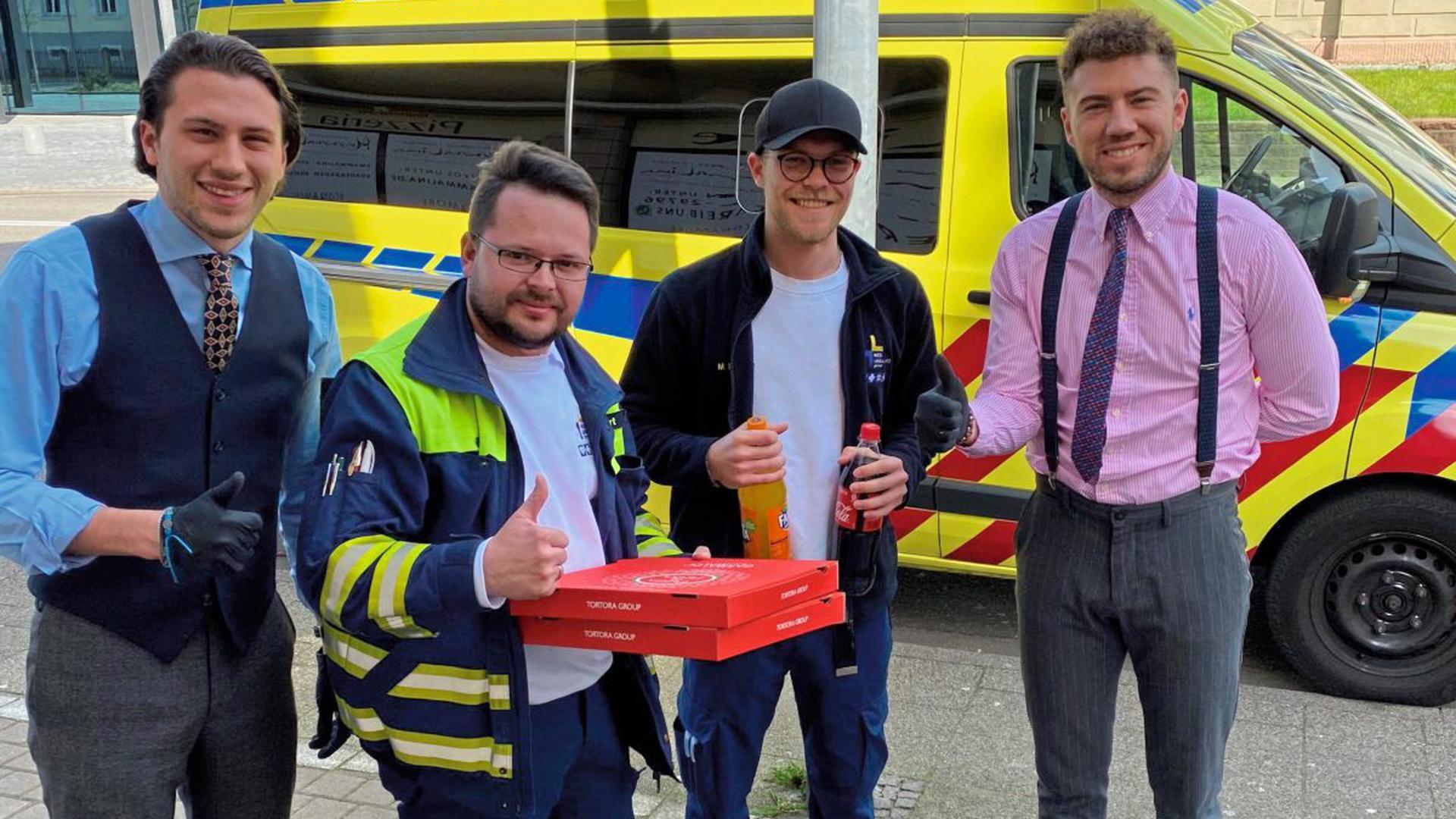 Roberto Mario Tortora (links) und sein Bruder Angelo Francesco Tortora mit zwei Notfallsanitätern und den Wunsch-Pizzen.