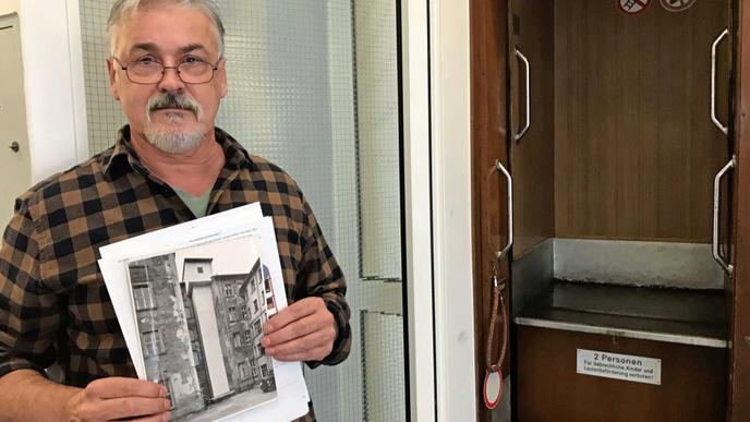 Objektmanager Rolf Kopf mit einem alten Foto aus der Bauzeit – rechts dahinter der Fahrstuhl, wie er heute aussieht.