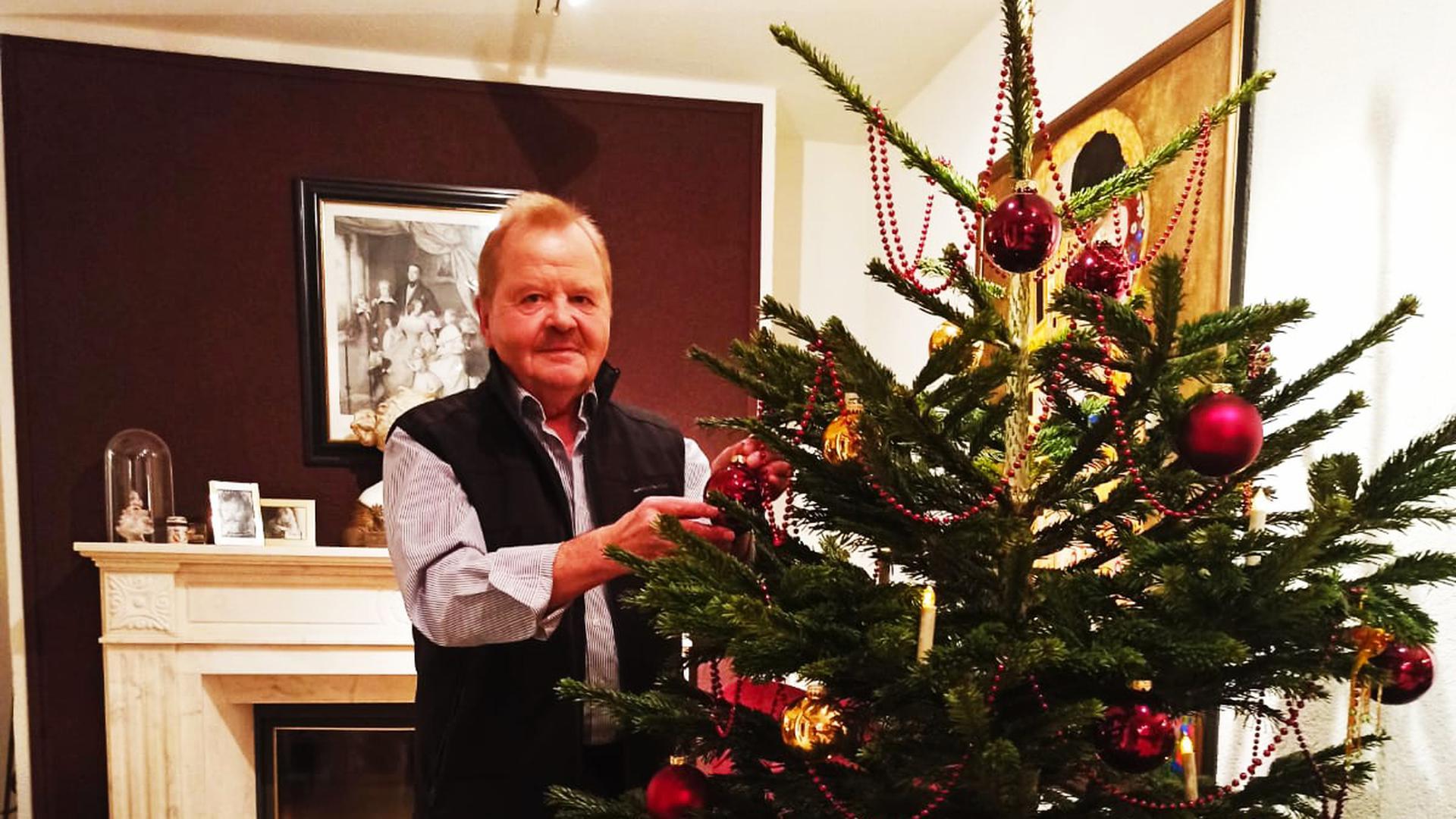 Mann mit Christbaum im Wohnzimmer