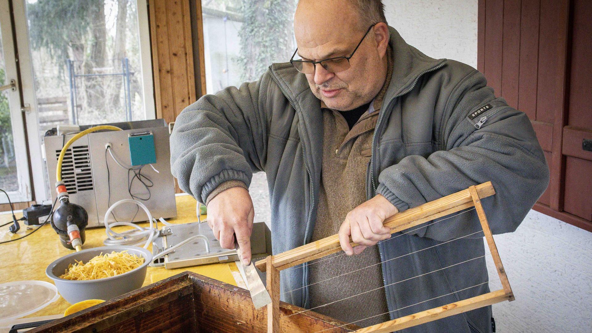 Der Söllinger Imker Holger Gebert säubert einen Wabenrahmen mit einem Stockmeisel