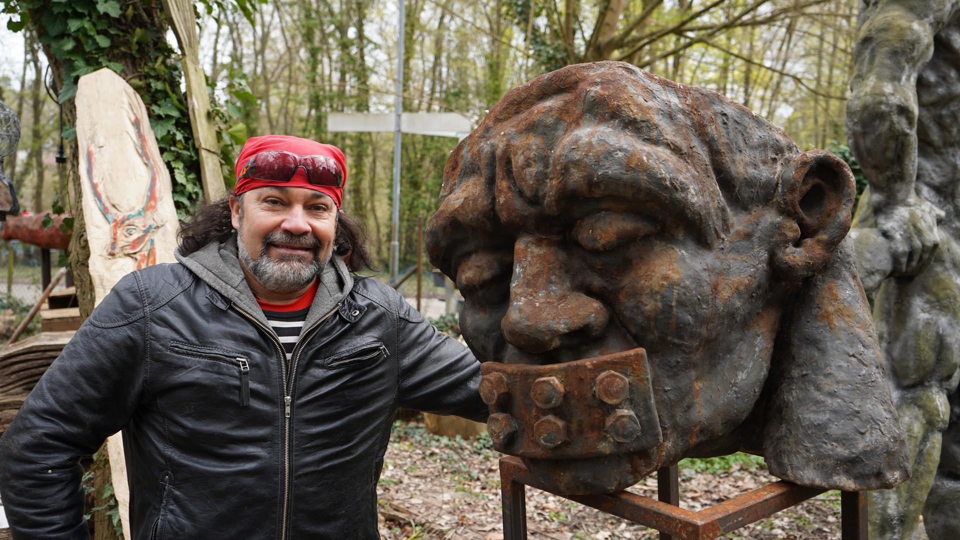 Mann mit Bart, Lederjacke und rotem Kopftuch neben einer Skulptur.