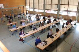 Gemeinderäte sitzen in Halle an separaten Tischen