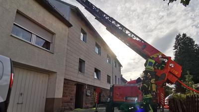 Ein Feuerwehr-Auto steht mit ausgefahrener Drehleiter an einem Wohnhaus.