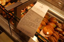 Der Kassenbeleg einer Bäckerei auf dem Tresen über den Verkaufswaren.