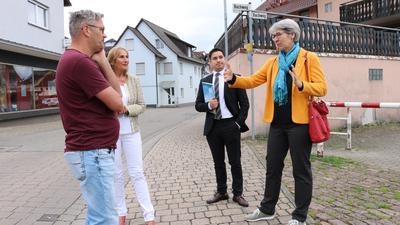 zwei Frauen und zwei Männer stehen auf einer gepflasterten Ortsstraße und diskutieren