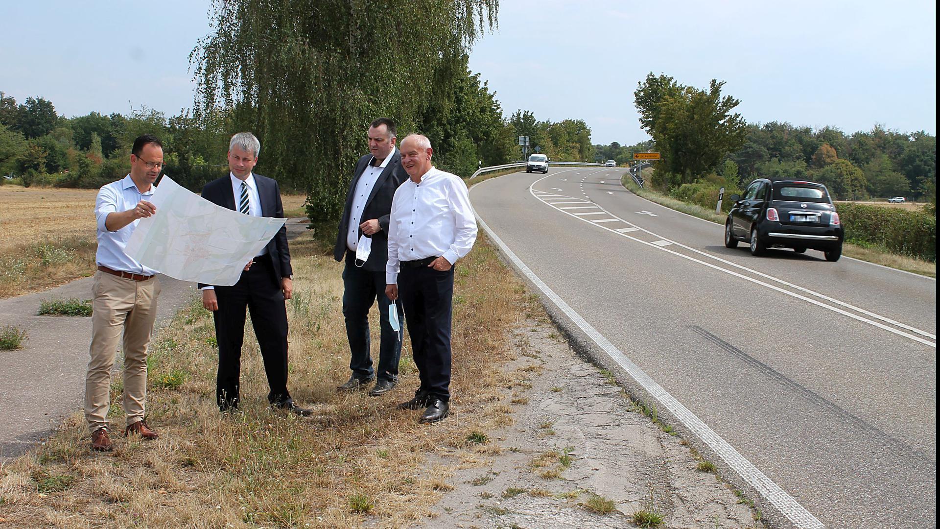 Vier Männer stehen an einer Straße in der Natur, zwei davon haben einen großen Faltplan ausgepackt und schauen darauf.