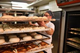 Ein Bäcker schiebt Bleche mit Brezeln und Brötchen auf einen Wagen.