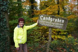Frau mit gelber Jacke lehnt an einem Schild, das einen Grenzverlauf beschreibt.
