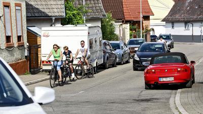 Fahrende Autos, Radfahrer, parkende Fahrzeuge in der Weingartener Straße in Jöhlingen