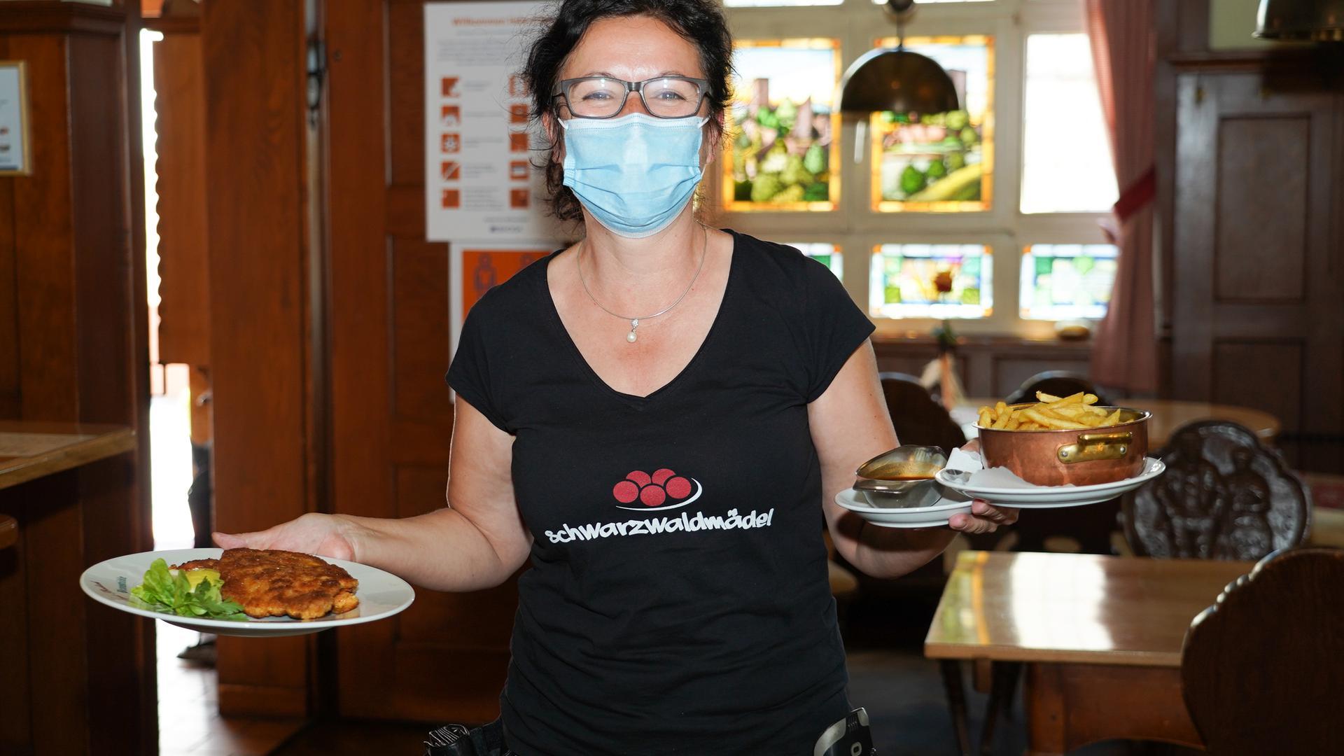 Mit Mundschutz werden in Bauhöfers Braustüb'l in Renchen-Ulm die Teller zu den hungrigen Gästen gebracht.