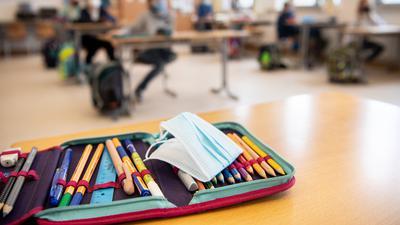 Der Ersatz-Mundschutz einer Schülerin liegt während des Unterrichts in einer vierten Klasse einer Grundschule auf dem Federmäppchen der Schülerin.