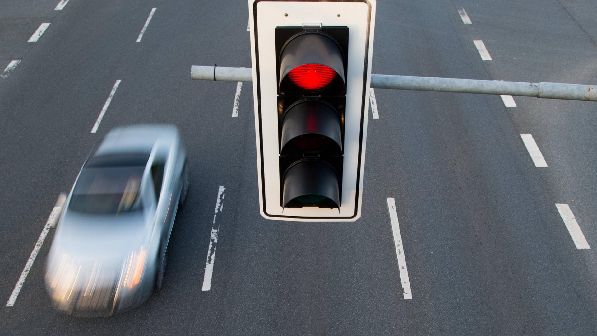 ARCHIV - 17.07.2013, Hannover: Ein Auto fährt an einer roten Ampel vorbei.  (zu dpa «Kommunen können bald selbst Rotsünder blitzen - Vorreiter Mainz» vom 28.02.2019) Foto: Julian Stratenschulte/dpa +++ dpa-Bildfunk +++ | Verwendung weltweit