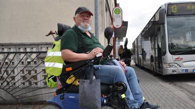 Ein Mann mit seinem Rollstuhl an der Bushaltestelle. Im Hintergrund fährt ein Bus ein.