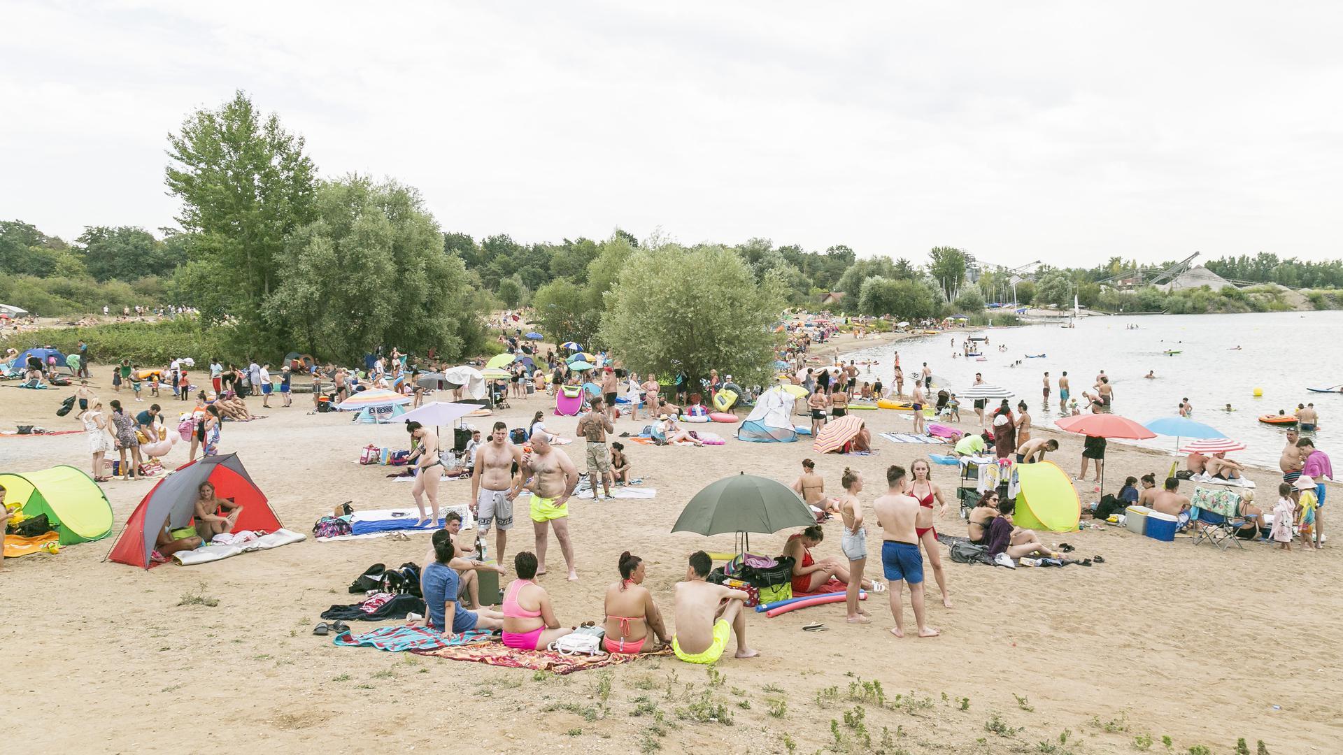 Blick auf einen Strand eines Baggersees, an dem viele Menschen sind.