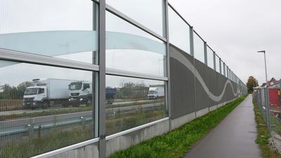 Drei weiße Lastwagen, Lärmschutzwand, kleiner Fahrradweg