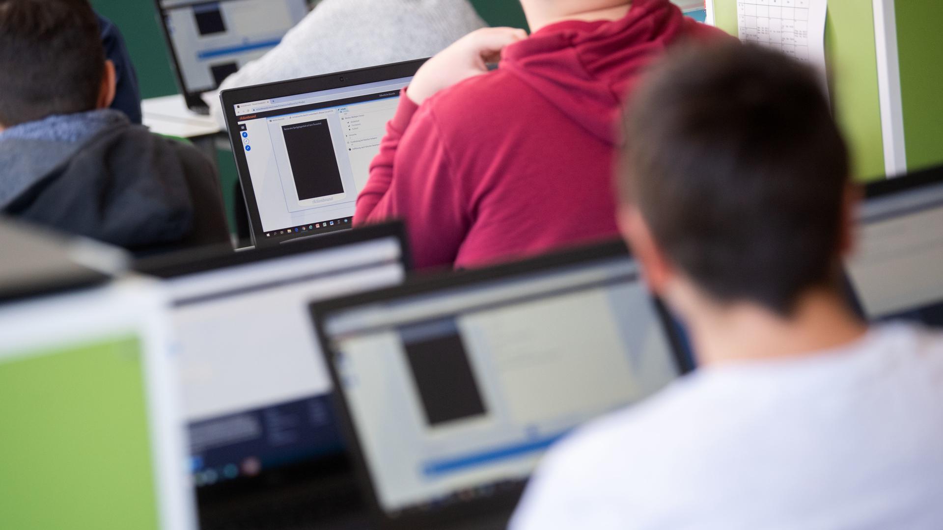 Schülerinnen und Schüler nehmen im Klassenzimmer einer 9. Klasse der Gemeinschaftsschule Leutenbach mm Geografieunterricht mit Hilfe von Laptops und Tablets teil.