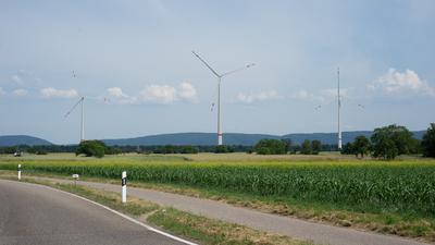 Drei Windräder stehen auf einem Feld