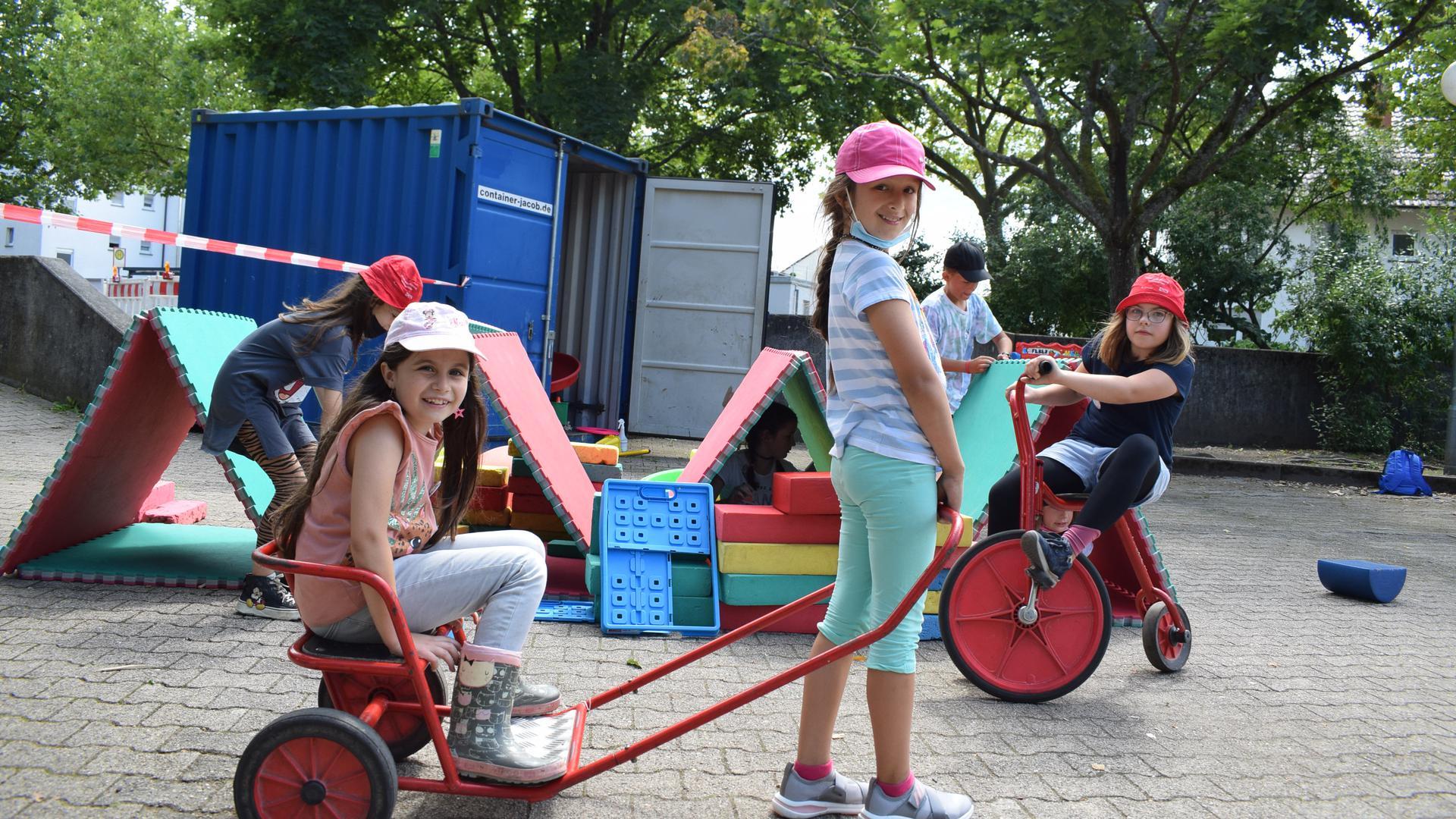 Mit der Rikscha über den Schulhof: Zwei Mädchen haben sichtlich Spaß bei der Stadtranderholung in Rheinstetten.