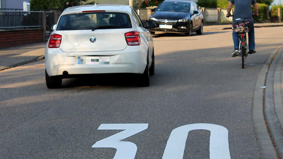 Ein Auto neben einem Radfahrer auf der Straße. Auf dem Boden steht eine große Dreißig.