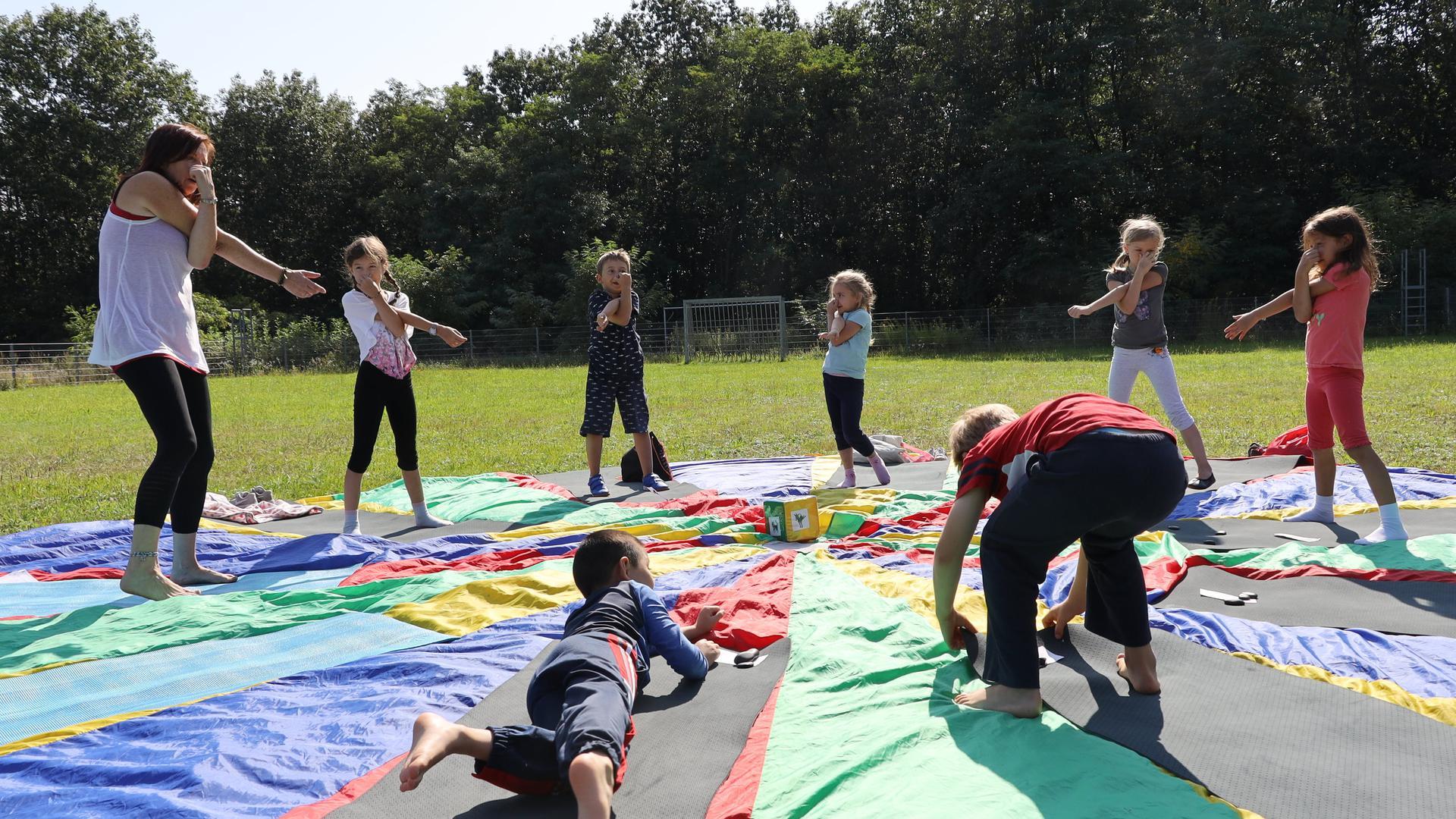Gruppe von Kinder machen Yoga im Freien.