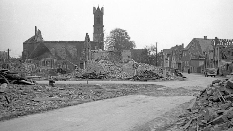 Das Ende des dörflichen Lebens: Die ausgebrannte Rintheimer Kirche ragt nach dem Luftangriff Ende April 1944 über zerstörten Häusern und ruinierten landwirtschaftlichen Nutzflächen auf.