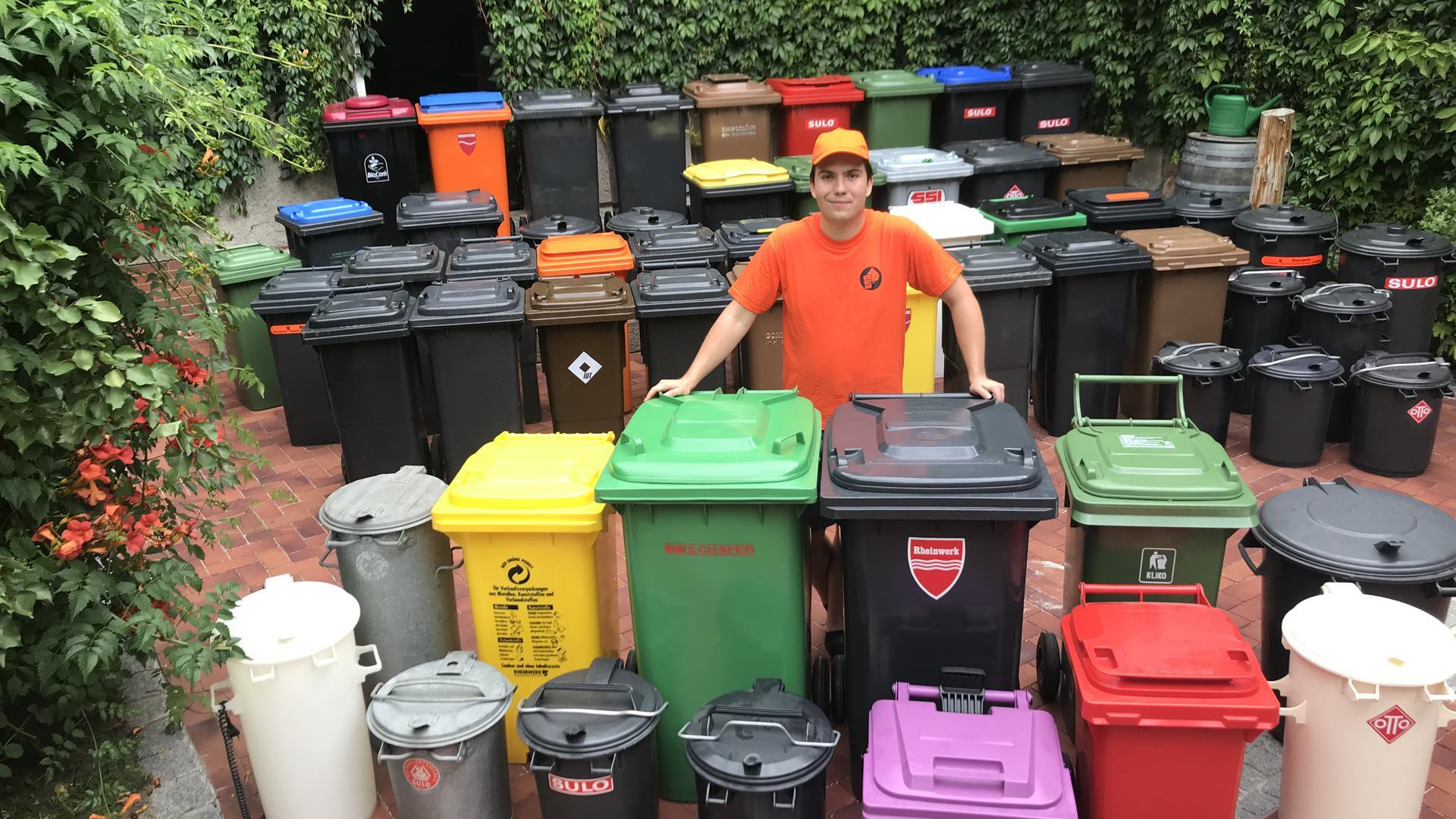 Ein junger Mann (Alexander Smoljanovic) steht inmitten vieler Mülltonnen.