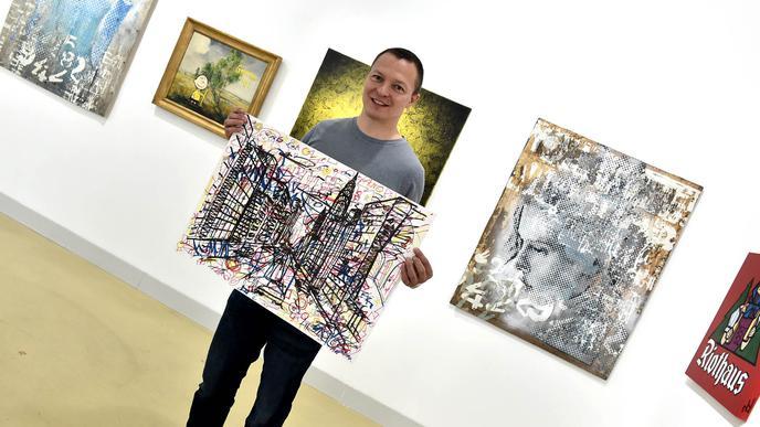 Christian Timm mit einer Zeichnung von Oliver Maichle, die er ausgestellt hatte.