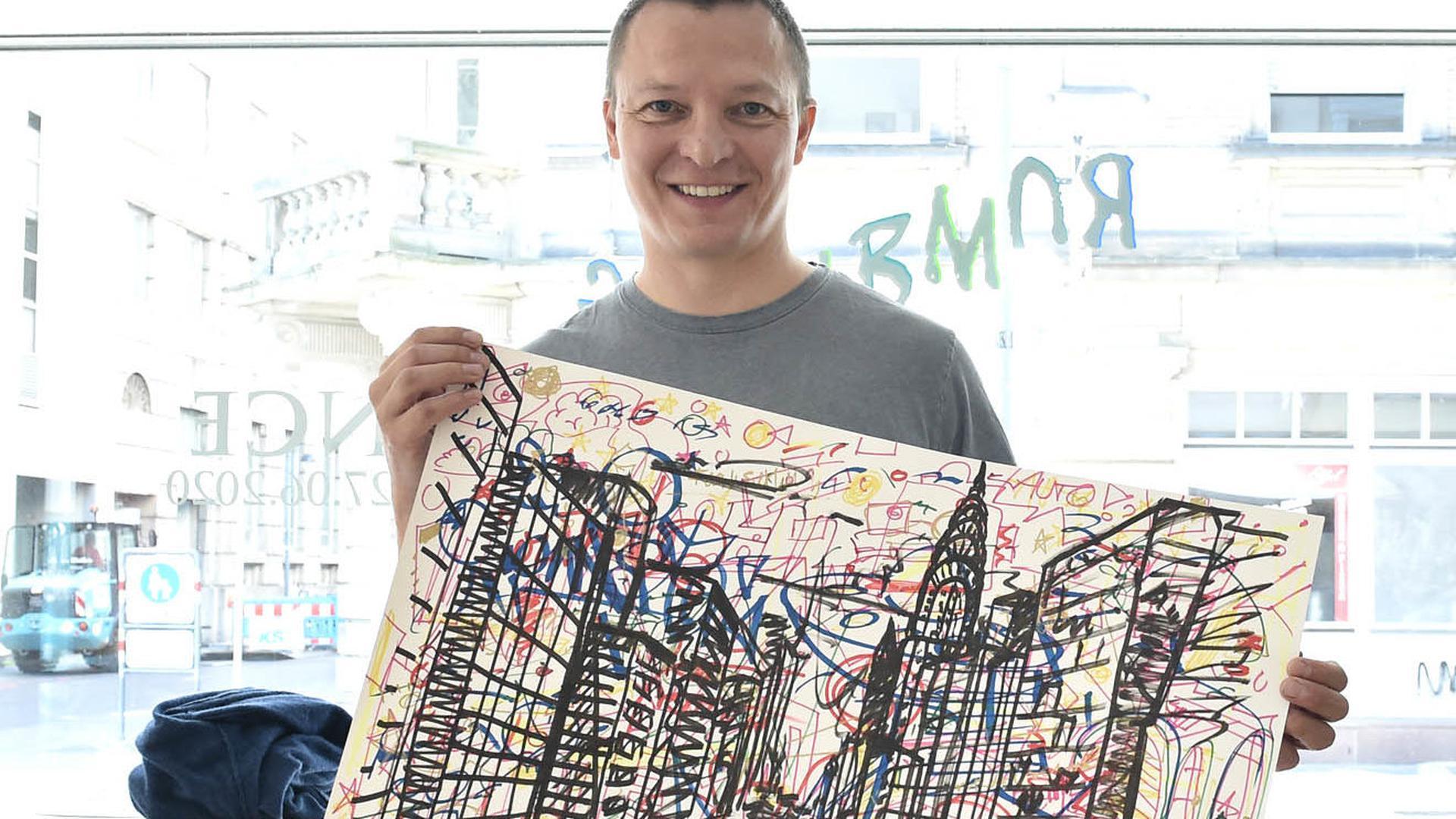 Christian Timm mit einer Zeichnung des Streetart-Künstlers Oliver Maichle.