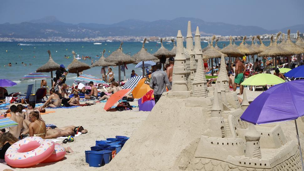 Touristen sonnen sich am Strand von El Arenal auf der Balearen-Insel Mallorca. Viele Touristen zieht es nach Spanien.
