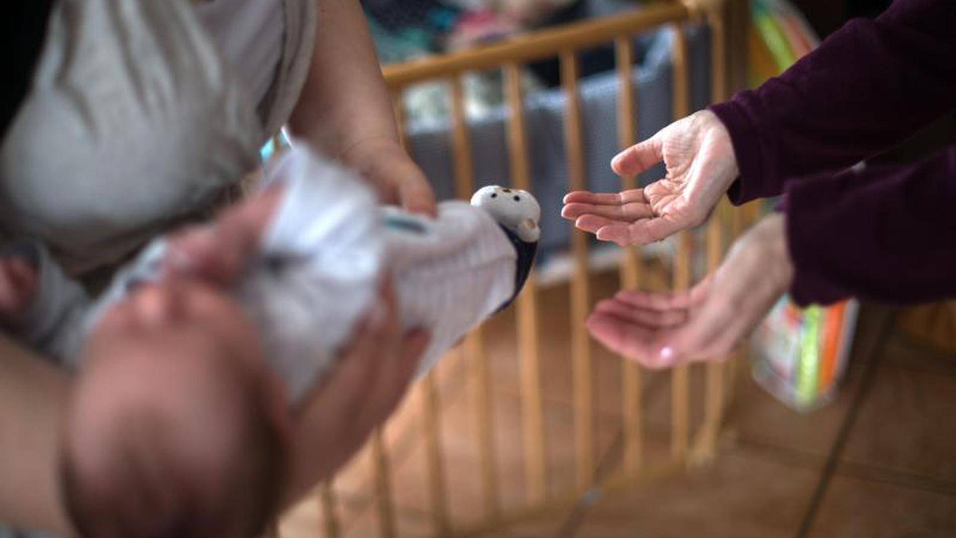 Hebamme lässt sich ein wenige Tage altes Kind überreichen