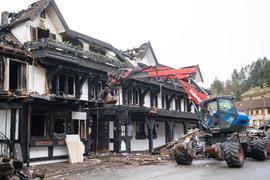 Ein Bagger räumt Schutt vor dem Eingang des ausgebrannten Restaurants weg.