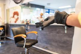 Eine Friseurmeisterin zieht sich Handschuhe zum Schutz an