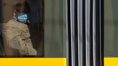 Ein Mann sitzt in der Straßenbahn und trägt einen Mundschutz.