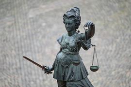Die Statue der Justitia mit einer Waage und einem Schwert in der Hand ist zu sehen.
