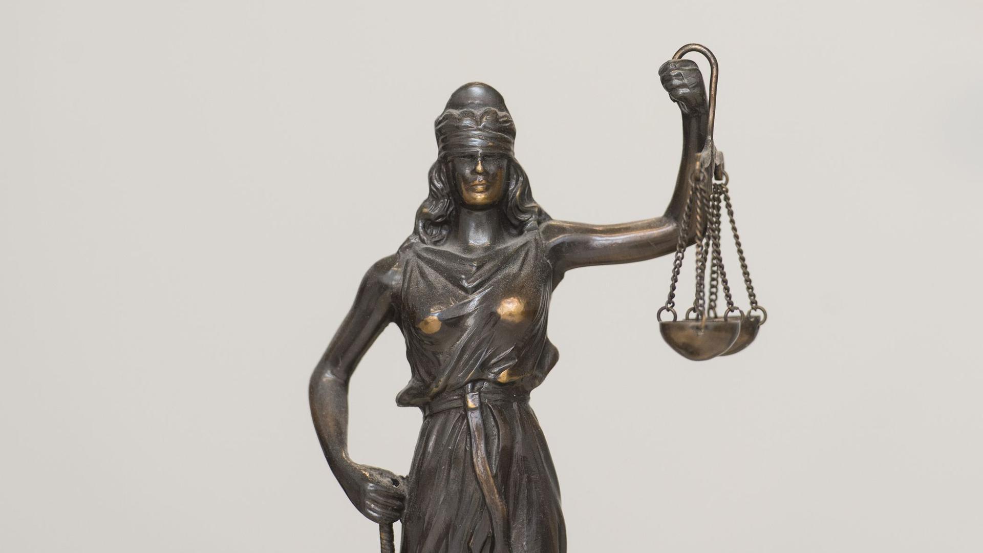 """Eine Figur """"Justitia"""" steht auf einem Schreibtisch."""