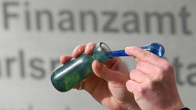 """EinMann hält vor dem Karlsruher Finanzamt einen Flakon mit Banknoten-Duft, das Parfüm """"Aerarium"""", in der Hand."""