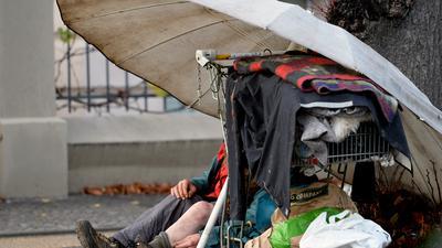 """ARCHIV - 24.11.2014, Brandenburg, Potsdam: Unter einem Schirm sitzt ein wohnungsloser Mann. Obdachloseneinrichtungen blicken mit Sorge auf den Winter in der Corona-Pandemie. (zu """"Obdachlosenunterkünfte vor dem Corona-Winter - Situation """"dramatisch"""""""") Foto: Ralf Hirschberger/dpa-Zentralbild/dpa +++ dpa-Bildfunk +++"""