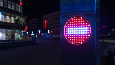 Ein Stop-Piktogramm an einer Rolltreppe leuchtet am späten Abend.