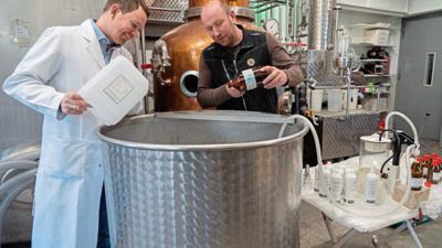 Kein Rotwein, aber dennoch alkoholisch: Ein Sasbachwaldener Winzer von der Alde-Gott-Brennerei füllt gemeinsam mit einem Mitarbeiter der Sasbacher Lender-Apotheke Desinfektionsmittel ab.