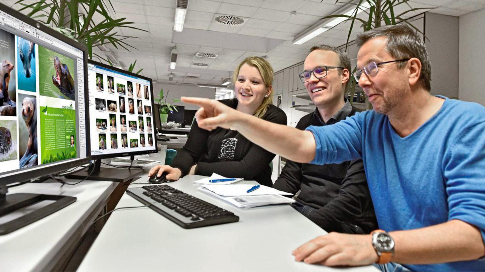 Ein Zoobuch entsteht: Der Bestsellerautor Mario Ludwig (rechts) informiert sich in der BNN-Technik bei Nina Nees und Volontär Anatol Fischer über die Arbeiten an dem neuen Bildband.