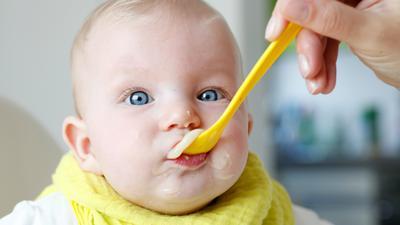Ein Baby wird mit einem Löffel Brei gefüttert.