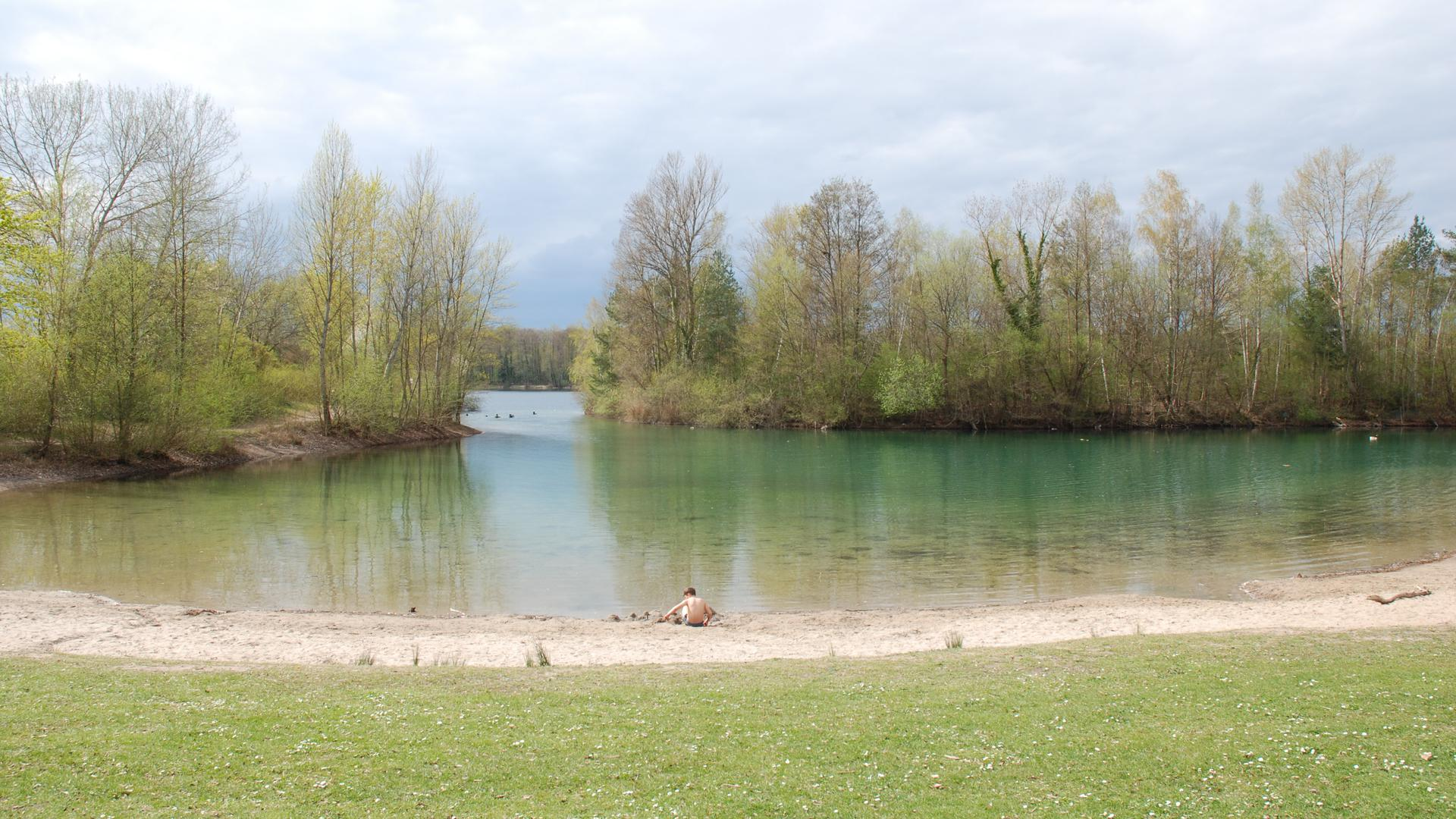 Ruhe vor der Badesaison: Das Bild zeigt Liegewiese, Sandstrand und Badebucht des Untergrombacher Baggersees.