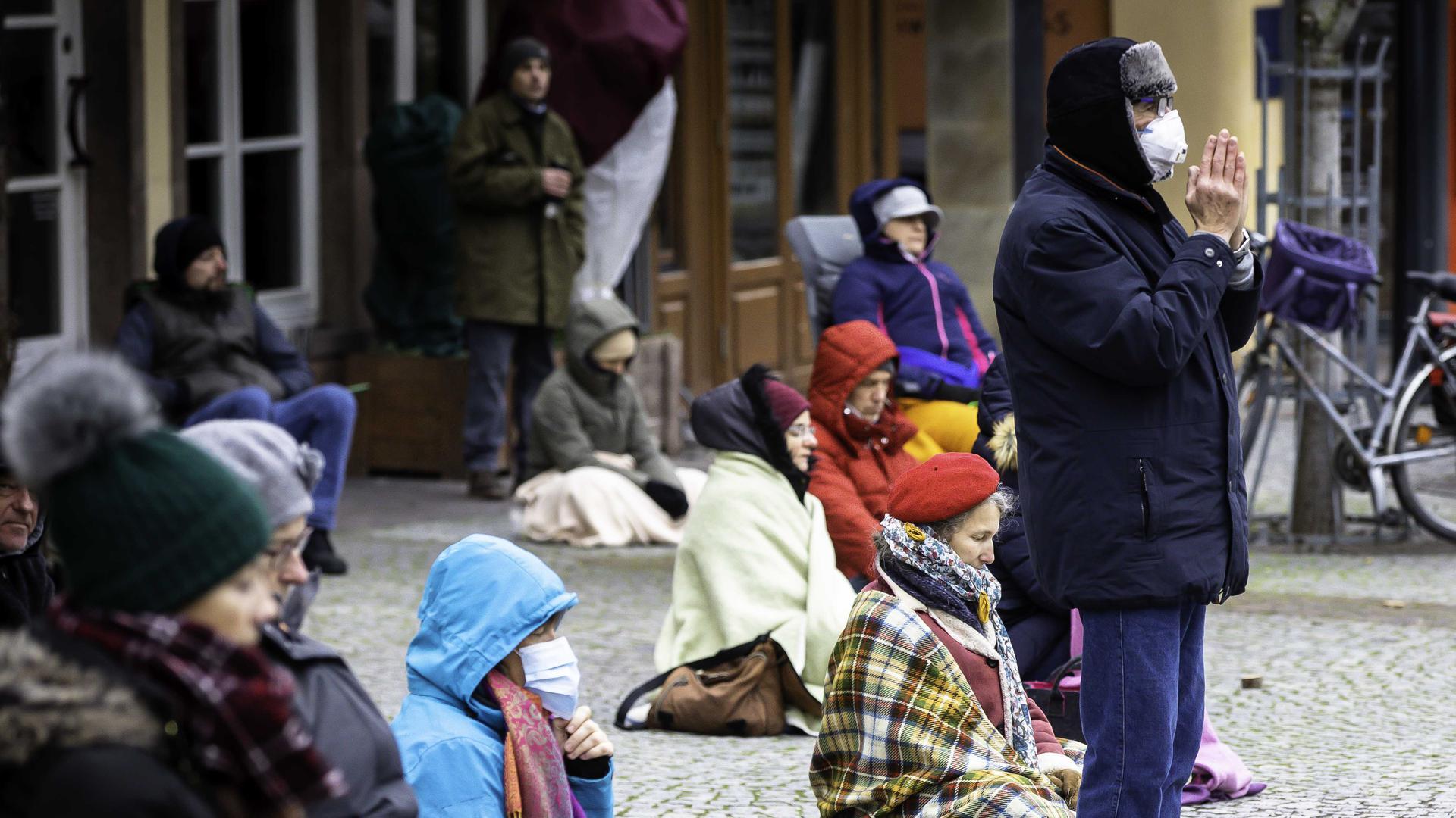 Warm angezogene Menschen sitzen auf dem Pflaster des Brettener Marktplatz, drum herum stehen Zuschauer.