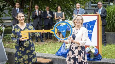 Die kommissarische Schulleiterin Nicole Roeder erhält einen symbolischen Schlüssel von ihrer ausscheidenden Vorgängerin Barbara Sellin (rechts). Die Abteilungsleiter applaudieren im Hintergrund.